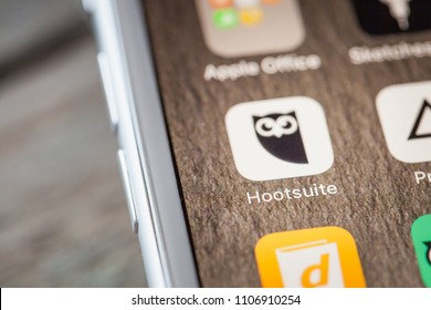 BERLIN, GERMANY - JUNE 6, 2018: Close up to social media planning and publishing tool HootSuite on the screen of an iPhone 7 Plus with personalized background.