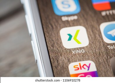 BERLIN, GERMANY - JUNE 6, 2018: Close up to Xing professional network app on the screen of an iPhone 7 Plus with personalized background.