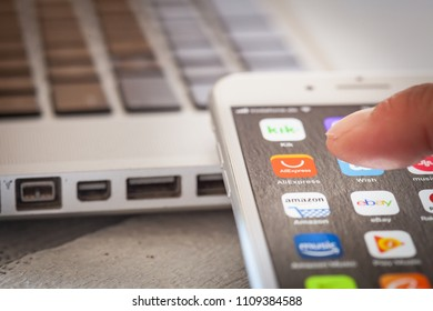 BERLIN, GERMANY - JUNE 6, 2018: Close up to male finger pressing icon to open Chinese trading app AliExpress on the screen of an iPhone 7 Plus with personalized background.