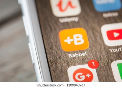 BERLIN, GERMANY - JUNE 6, 2018: Close up to interatctive language learning app Babbel on the screen of an iPhone 7 Plus with personalized background.
