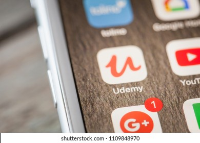 BERLIN, GERMANY - JUNE 6, 2018: Close up to Udemy online learning videos tutorials app on the screen of an iPhone 7 Plus with personalized background.