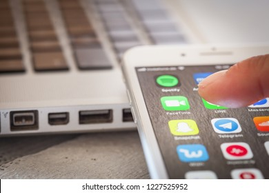 BERLIN, GERMANY - JUNE 6, 2018: Close up to male finger pressing icon to open Facetime app on the screen of an iPhone 7 Plus with personalized background.