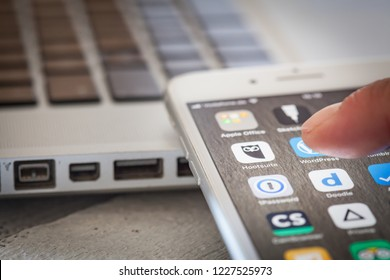 BERLIN, GERMANY - JUNE 6, 2018: Close up to male finger pressing icon to open HootSuite app on the screen of an iPhone 7 Plus with personalized background.