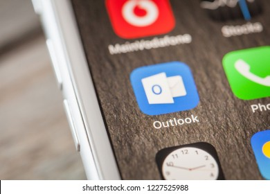 BERLIN, GERMANY - JUNE 6, 2018: Close up to Microsoft Outlook app on the screen of an iPhone 7 Plus with personalized background.