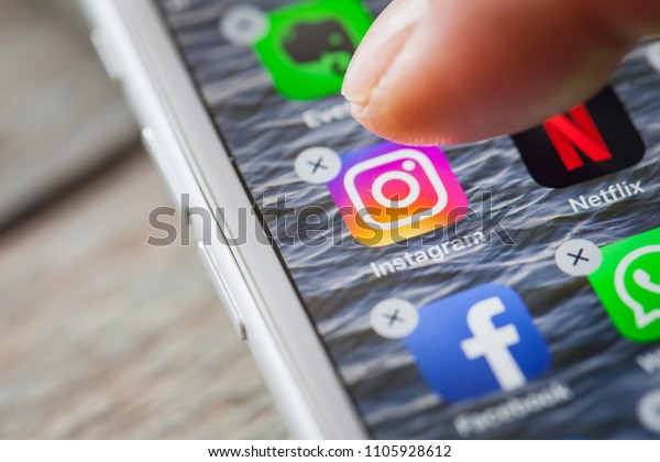 BERLIN, GERMANY - JUNE 6, 2018: Close up to finger deleting the Instagram on the screen of an iPhone 7 Plus with personalized background.