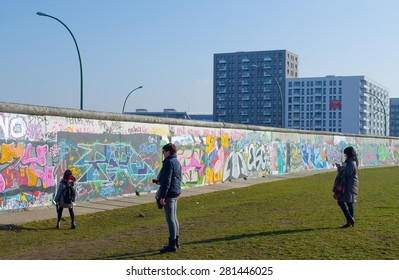 BERLIN, GERMANY, MARCH 12, 2015: people are admiring wall paintings situated on the east side gallery in berlin.