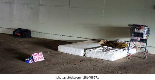 BERLIN, GERMANY, MARCH 12, 2015: homeless person in berlin built his modest household under the bridge. mattress, shopping cart and sign for food donation is the only equipment.