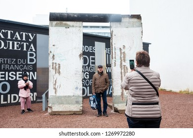 BERLIN, GERMANY - MARCH, 2018: Tourists looking at a piece of the Berlin Wall at the  entrance of the BlackBox Cold War Museum