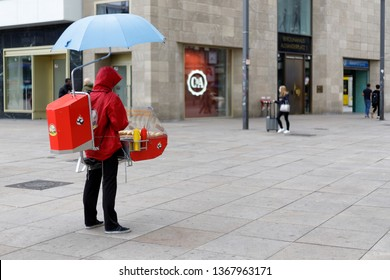 Berlin, Germany - March 24, 2019: Hotdog vendor with vendor's tray and umbrella at Alexanderplatz in the rain