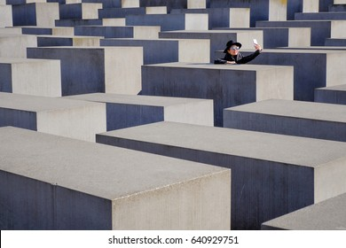 BERLIN, GERMANY - MARCH 26, 2017: Beautiful Woman Tourist selfie at Holocaust Memorial to the Murdered Jews of Europe  in daylight at 26 March 2017, Berlin, Germany