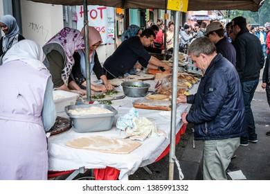 Berlin, Germany - May 01, 2019: Women preparing food on street market at myfest, labor day parade  on 1. mai, Berlin, Kreuzberg