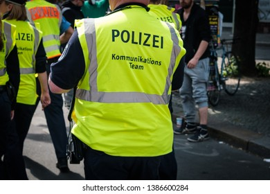 Berlin, Germany - May 01, 2019: German police from behind in crowded street parade on labor day in Berlin