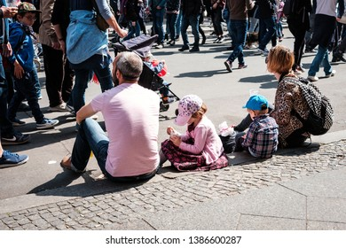 Berlin, Germany - May 01, 2019: Young family with children sitting on sidewalk on street parade on labor day in Berlin