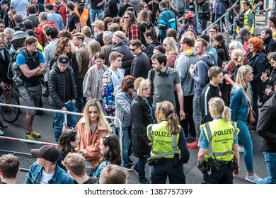 Berlin, Germany - May 01, 2019:  Many people and  police women at entrance to street fest on labor day in Berlin, Kreuzebrg