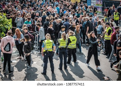 Berlin, Germany - May 01, 2019:  Crowd of people and  police women at entrance to myfest celebration on labor day in Berlin, Kreuzebrg