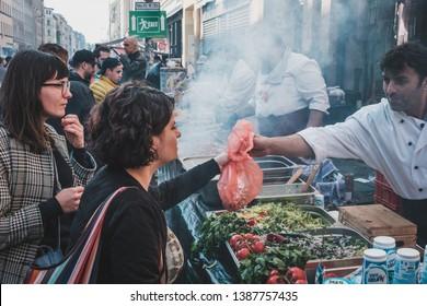 Berlin, Germany - May 01, 2019: Girl buying turkish street foodin Berlin, Kreuzberg on labor day
