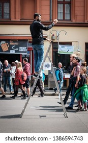 Berlin, Germany - May 01, 2019:Man standing on ladder taking picture with mobile phone on street parade on labor day in Berlin