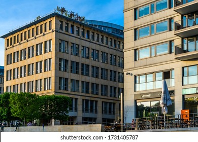 Berlin, Germany - May 1, 2019: The view of two modern yellow houses with trees on the roof. The cafe on the promenade of the Spree river.