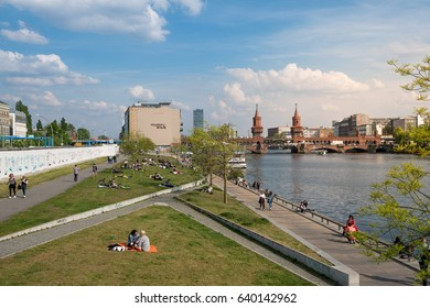 Berlin, Germany - may 12, 2017: People relaxing at river Spree, next to the  Berlin wall (East Side Gallery) and Oberbaum Bridge on a summer day in Berlin, Germany