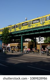BERLIN, GERMANY - MAY 12, 2018: an U-Bahn (metro) train at Eberswalder Strasse station in Berlin's Prenzlauer Berg district, with the famous Konnopke's fast food stand visible below.