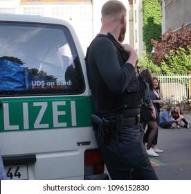 Berlin, Germany - May 19, 2018: Back turned German policeman (Polizei) at work during the Carnival of Cultures (Karneval der Kulturen), multicultural festival in Kreuzberg, Berlin