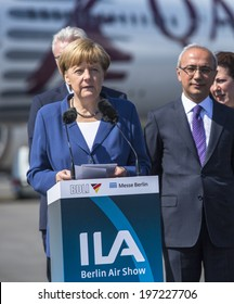 BERLIN, GERMANY - MAY 20, 2014: German Chancellor Angela Merkel (L) and Turkish Minister of transport Lutfi Elvan (R) open up the International aviation and space exhibition ILA.