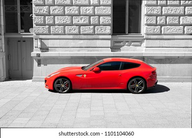 Berlin, Germany, May 2018 - Ferrari F12 Berlinetta in Rosso Corsa Red - Color isolated in front of a building in black and white