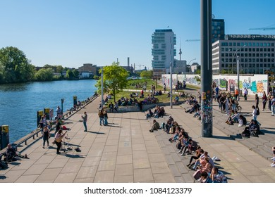 Berlin, Germany - may, 2018:  Many people at river Spree at Berlin Wall ( East Side Gallery) on a sunny day in Berlin, Germany