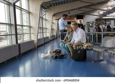 Berlin, Germany: May 23, 2015: A mature couple are sitting in an airport lounge with a small white dog sitting at their feet. Tegel Airport is the main International Airport of Berlin.