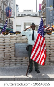 BERLIN, GERMANY - MAY 23: A man dressed as a US Army soldier stands with an American flag at the former Allied checkpoint 'Charlie' on May 23, 2014. Nowadays this site is a tourist attraction.
