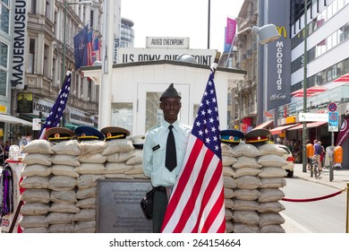 BERLIN, GERMANY - MAY 23: Man dressed as a US Army soldier stands with an American flag at the former Allied checkpoint 'Charlie' on May 23, 2014. Nowadays this site is a tourist attraction.
