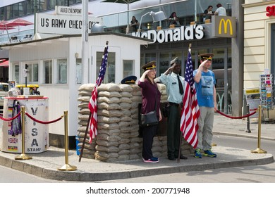 BERLIN, GERMANY - MAY 23: Tourists posing at the former Allied checkpoint 'Charlie' on May 23, 2014. Nowadays this site is a tourist attraction.