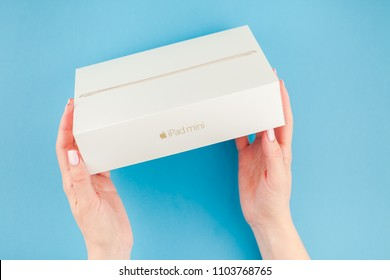 BERLIN, GERMANY - MAY 24, 2018: Woman hands holding box of the latest Ipad mini against bright blue background. Unboxing present concept with copy space