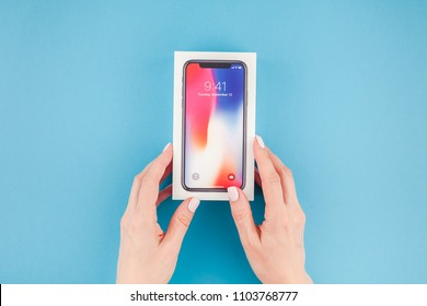 BERLIN, GERMANY - MAY 24, 2018: Woman hands holding the colorful box of the latest Apple iPhone X 10 smartphone against bright blue background. Unboxing concept with copy space