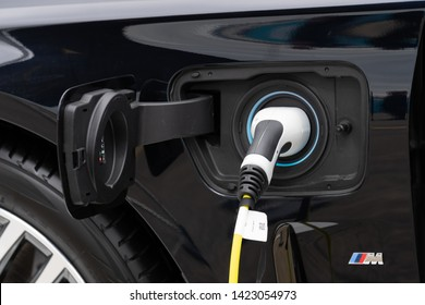 Berlin, Germany - May 25, 2019: Detail of a black BMW M electric car being charged at station. BMW M GmbH (previously BMW Motorsport GmbH) is a subsidiary of German car manufacturer BMW AG