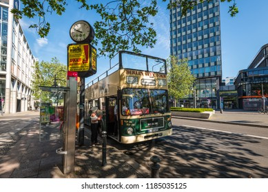 Berlin, Germany - May 27, 2017: Hop-on Hop-off sightseeing bus Berlin City Tour in the city street waiting for tourists at a stop in Berlin, Germany.