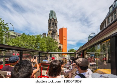 Berlin, Germany - May 28, 2017: People look at the sights of Berlin by Hop-on Hop-off bus - go along the Kurfurstendamm avenue in Berlin, Germany. Kaiser-Wilhelm-Kirche church in the center.