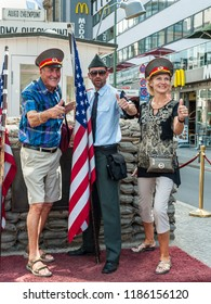 Berlin, Germany - May 28, 2017: Tourists on the street near soldier at Checkpoint Charlie in Berlin. Checkpoint Charlie famous passage between the West and East Berlin during the Cold War.