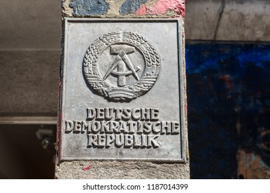 Berlin, Germany - May 28, 2017: The national emblem of the German Democratic Republic (East Germany) featuring a hammer and a compass, surrounded by a ring of rye on the border post in Berlin.