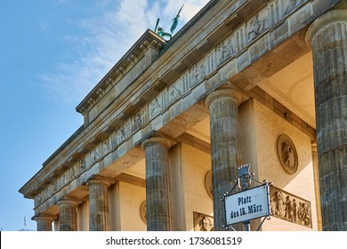 Berlin, Germany, May 6., 2020: Backlit view of the Brandenburg Gate with a sign with the German inscription: Platz des 18. März (Place of march 18)