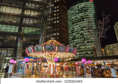 BERLIN, GERMANY - NOVEMBER 13, 2018: People visit night Christmas market with carousel on Potsdamer Platz. It is an important public square and traffic intersection in the city centre.