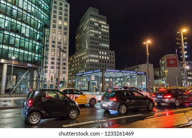 BERLIN, GERMANY - NOVEMBER 13, 2018: City night traffic on Potsdamer Platz. Entrance to the railway station on one of the main public square and traffic intersection.