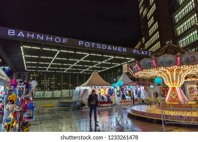 BERLIN, GERMANY - NOVEMBER 13, 2018: People visit night Christmas market with carousel on Potsdamer Platz. Entrance to the railway station on one of the main public square and traffic intersection.