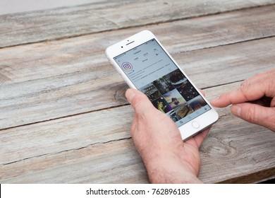 BERLIN, GERMANY - NOVEMBER 26, 2017: Man using Instagram app on iPhone 7 Plus at a desk