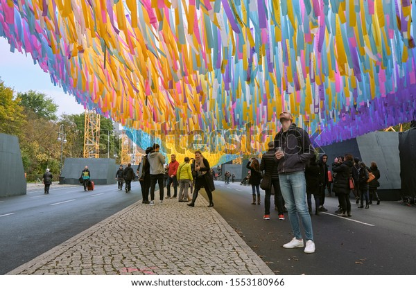 """Berlin, Germany - November 7, 2019: Visitors of the art installation """"Visions in Motion"""" at the Brandenburg Gate during the celebration of the 30th anniversary of the fall of the Berlin Wall"""