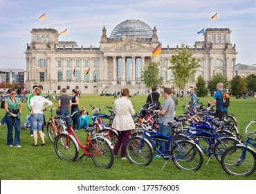 BERLIN, GERMANY - OCTOBER 02, 2012 : Unidentified bicycle riders near Berlin parliament building on October 02, 2012. Bicycles are the best way to see the most Berlin interesting sites.
