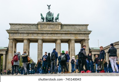 Berlin, Germany - October 10, 2017: young people walking near Brandenburg Gate constructed in 1788-1791, Pariser Platz, Mitte district. Rainy day in Berlin