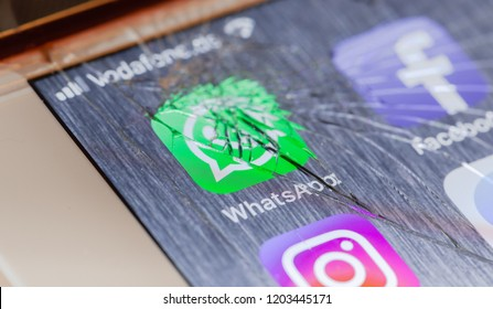 BERLIN, GERMANY - OCTOBER 15, 2018: WhatsApp app on a broken screen of an iPhone 7 Plus with personalized background, symbolic for system failure or defect
