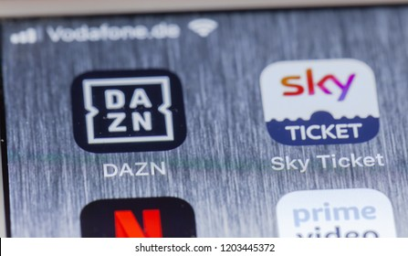 BERLIN, GERMANY - OCTOBER 15, 2018: DAZN and Sky Ticket, competing sports event streaming apps on screen of an iPhone 7 Plus with personalized background