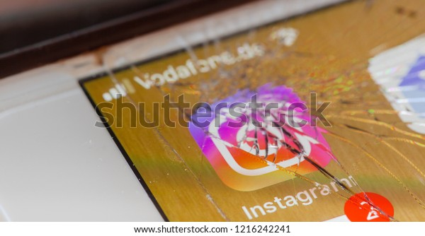 BERLIN, GERMANY - OCTOBER 20, 2018: Instagram app on a broken screen of an iPhone 7 Plus with personalized background, symbolic for system failure or defect